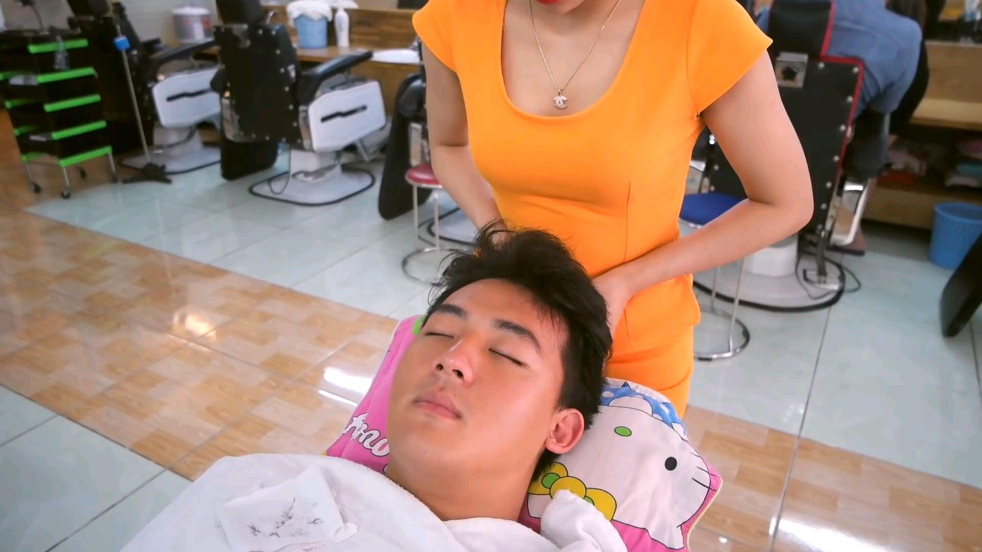 小哥在理发店里享受按摩,话说这个项链挺漂亮的